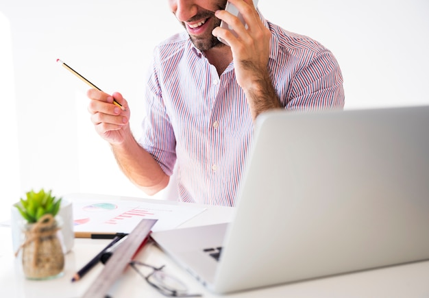 Bedrijfsmens die met een mobiele telefoon en laptop werken