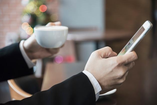 Bedrijfsmens die mobiele telefoon met behulp van terwijl het drinken van koffie in koffiewinkel