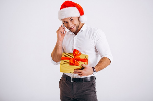 Bedrijfsmens die op telefoon in santahoed spreken die op witte achtergrond wordt geïsoleerd
