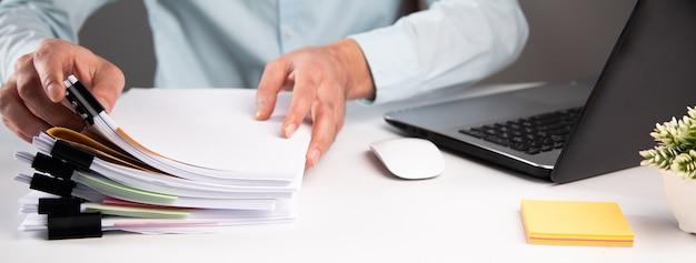 Bedrijfsmens die zakendocument dossier met laptop computer houden