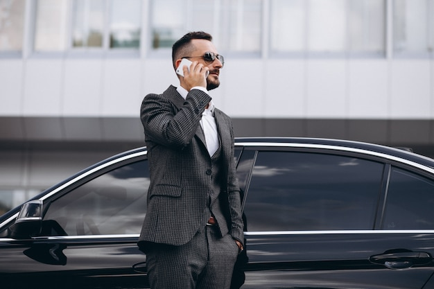 Bedrijfsmens door de auto die op de telefoon spreekt