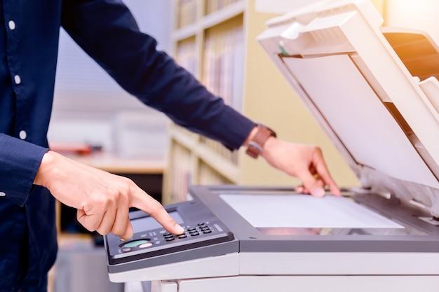 Bedrijfsmens drukknop op paneel van printer ,.