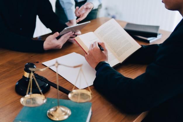 Bedrijfsmens en team en advocaten die contractdocumenten bespreken met messingsschaal op houten bureau in bureau