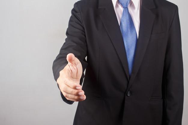 Bedrijfsmens het schudden handen op grijze achtergrond