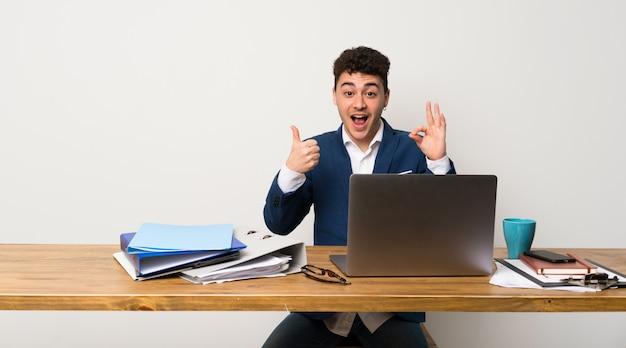 Bedrijfsmens in een bureau die ok teken en duim op gebaar tonen