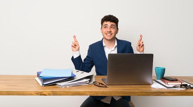 Bedrijfsmens in een bureau met vingers die en het beste kruisen wensen