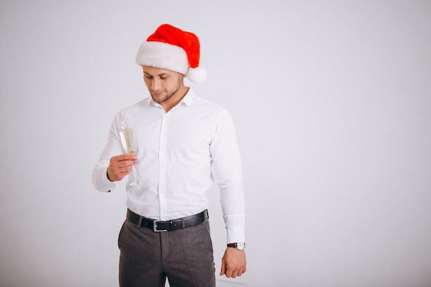 Bedrijfsmens in santahoed met glas van champaigne