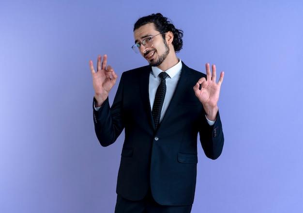 Bedrijfsmens in zwart kostuum en glazen die aan de voorzijde glimlachen die ok teken met beide handen maken die zich over blauwe muur bevinden