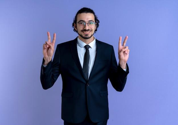 Bedrijfsmens in zwart kostuum en glazen die aan de voorzijde lacht die vrolijk overwinningsteken toont met beide handen die zich over blauwe muur bevinden