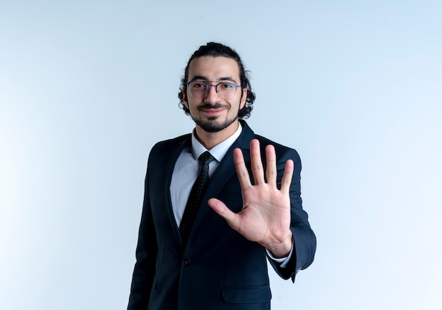 Bedrijfsmens in zwart kostuum en glazen die en met vingers nummer vijf tonen die die zich over witte muur glimlachen benadrukken