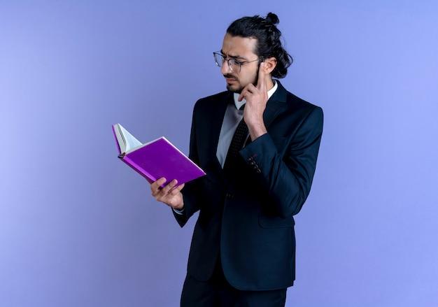 Bedrijfsmens in zwart kostuum en glazen die notitieboekje houden die het met ernstig gezicht bekijken die zich over blauwe muur bevinden