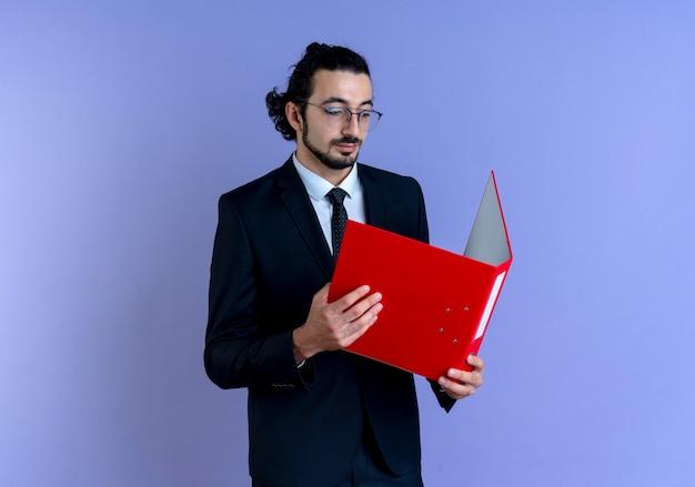 Bedrijfsmens in zwart kostuum en glazen die rode omslag houden die het met ernstig gezicht bekijkt dat zich over blauwe muur bevindt