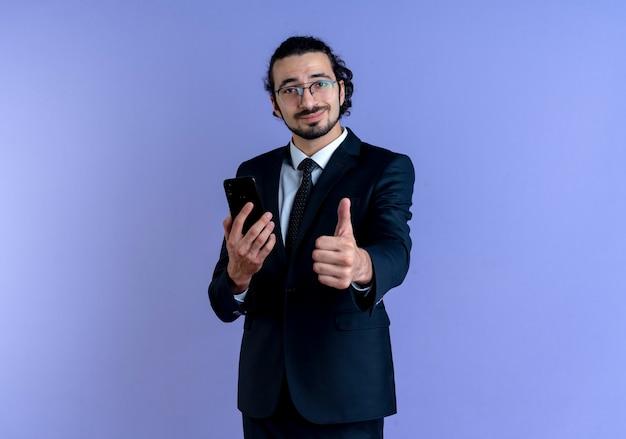 Bedrijfsmens in zwart kostuum en glazen die smartphone houden die aan de voorzijde kijken die duimen die omhoog glimlachen staande over blauwe muur tonen