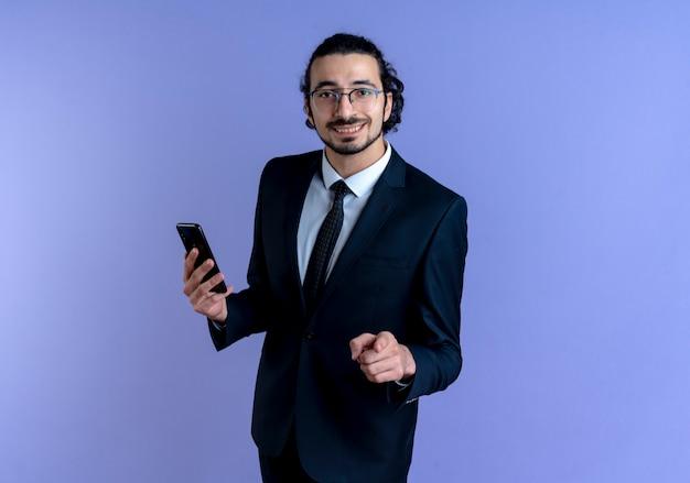 Bedrijfsmens in zwart kostuum en glazen die smartphone tonen die met vinger naar de voorzijde richt die zich zelfverzekerd over blauwe muur bevinden glimlachen