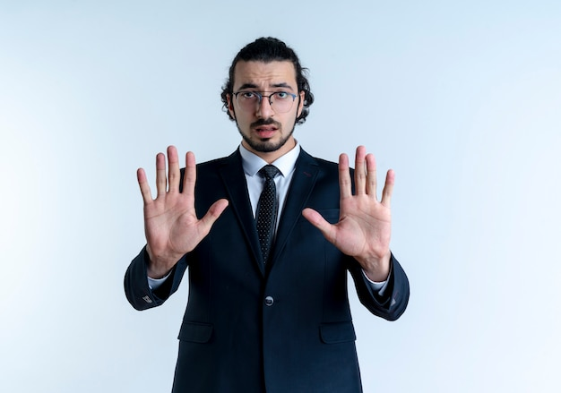 Bedrijfsmens in zwart kostuum en glazen die stopbord met beide handen maken die naar de voorzijde met ernstig gezicht kijken dat zich over witte muur bevindt