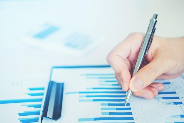 Bedrijfsmens met rapportgrafiek in bureau die nieuw bedrijfsproject plannen