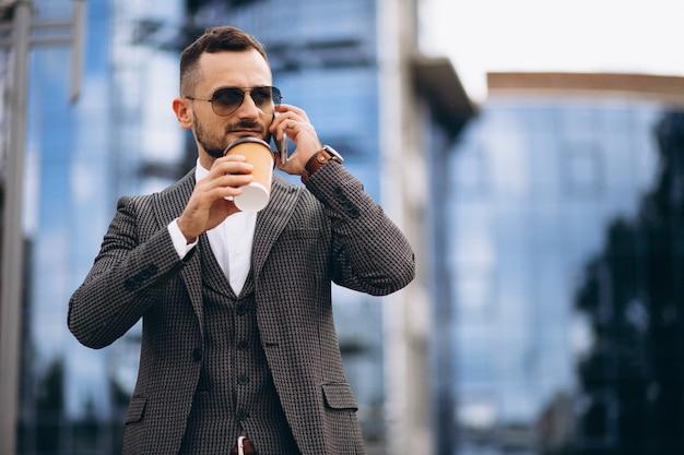 Bedrijfsmens met telefoon het drinken koffie buiten wolkenkrabber
