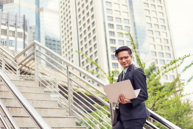 Bedrijfsmens met zijn laptop die de treden in een spitsuur opgaan om te werken