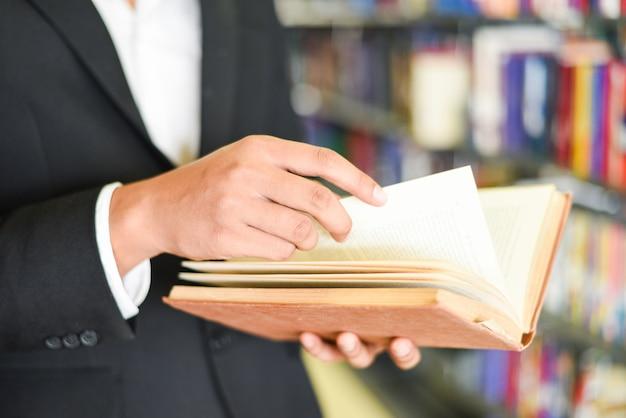 Bedrijfsmens of student die een boek bij de hand houden - van de het conceptenmens van de bedrijfsonderwijsstudie het lezingsboek met boekenrek in de bibliotheek