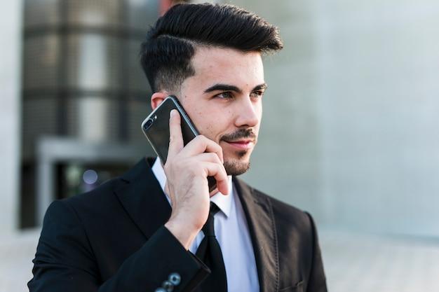 Bedrijfsmens voor het bureaugebouw die zijn mobiele telefoon gebruiken