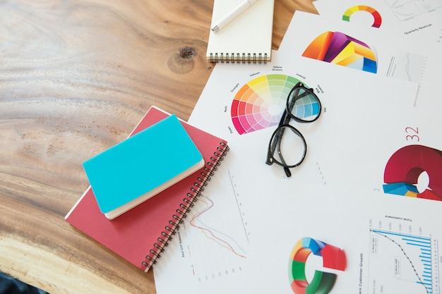 Bedrijfsmens werkplaats met grafiek, oogglazennotitieboekje en pen op houten bureau.