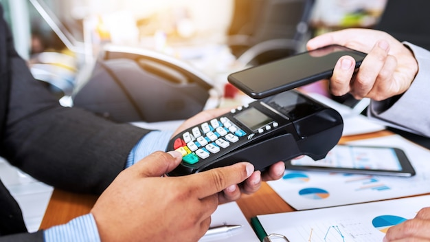 Bedrijfsmensbetaling door nfc-technologie met de machine van de creditcardlezer en smartphoneapp.