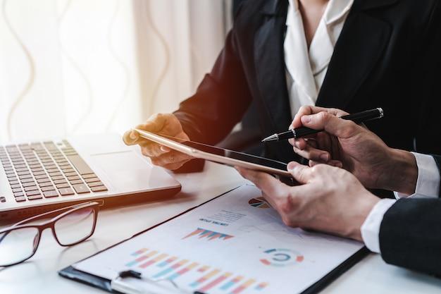 Bedrijfsmensen die aan bureaubureau werken met de analyse van grafiekgrafiekstatistieken