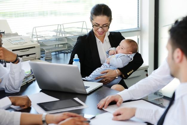 Bedrijfsmensen die baby in bureau behandelen