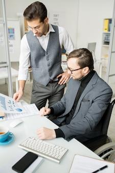 Bedrijfsmensen die bedrijfsgrafieken onderzoeken