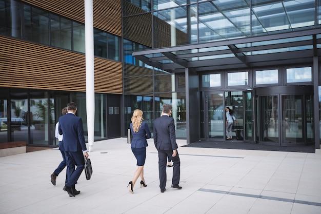 Bedrijfsmensen die binnen aan een bureaugebouw ingaan