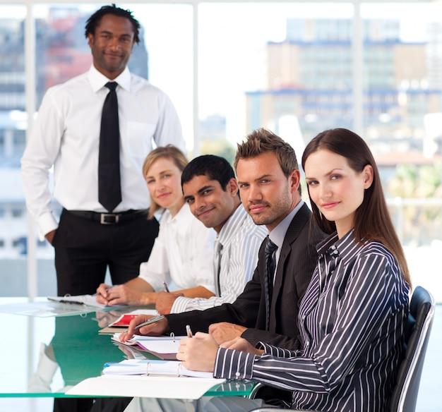 Bedrijfsmensen die de camera in een vergadering bekijken