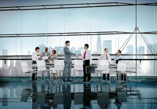Bedrijfsmensen die de groet van de besprekingshanddruk ontmoeten