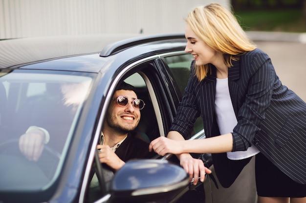 Bedrijfsmensen die dichtbij parkeerterrein spreken. de man met de bril zit in de auto, de vrouw staat naast hem