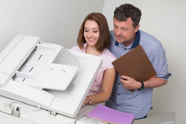 Bedrijfsmensen die een kopieermachine op het werk met behulp van