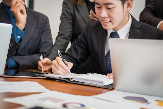 Bedrijfsmensen die een vergadering, een zakenman en een onderneemster hebben die met financieel grafiekrapport werken