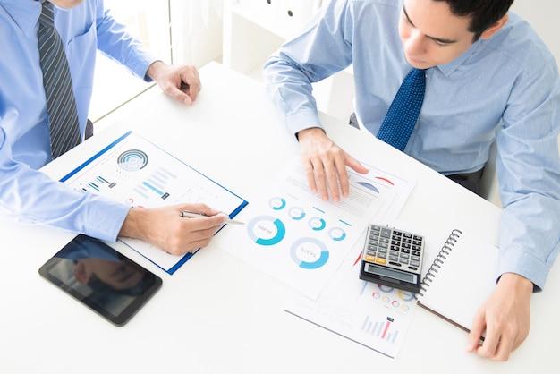 Bedrijfsmensen die financiële documenten bespreken en analyseren