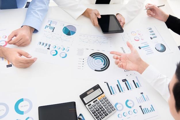 Bedrijfsmensen die financiële grafiekdocumenten bespreken en analyseren