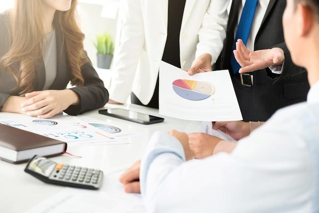 Bedrijfsmensen die financiële grafieken analyseren en bespreken