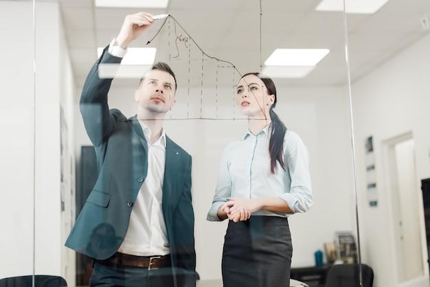 Bedrijfsmensen die grafiek op glasmuur analyseren
