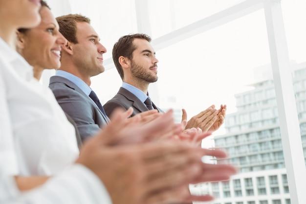 Bedrijfsmensen die handen in bureau slaan
