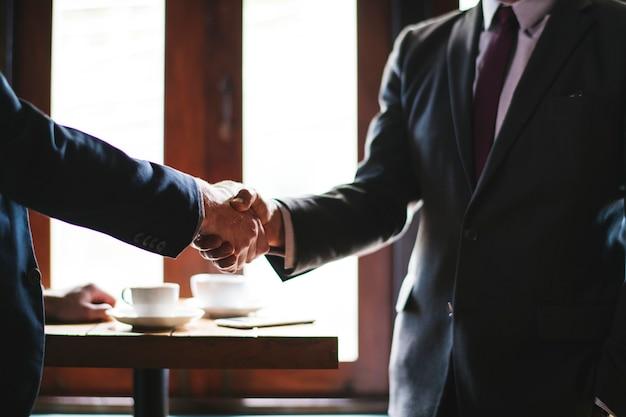 Bedrijfsmensen die handen in een vergaderzaal schudden