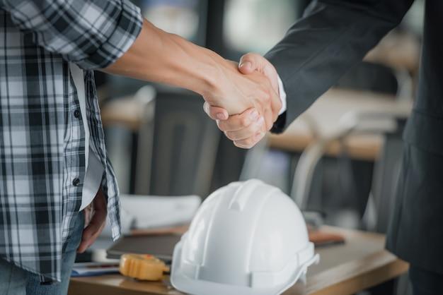 Bedrijfsmensen die handen samen boven bureau schudden.