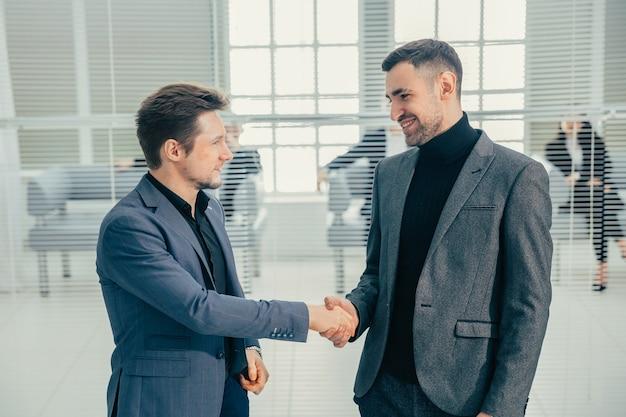 Bedrijfsmensen die handen schudden die zich in de bureaulobby bevinden. bedrijfsconcept.