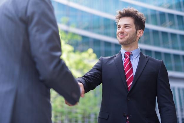 Bedrijfsmensen die handen voor een bureau schudden