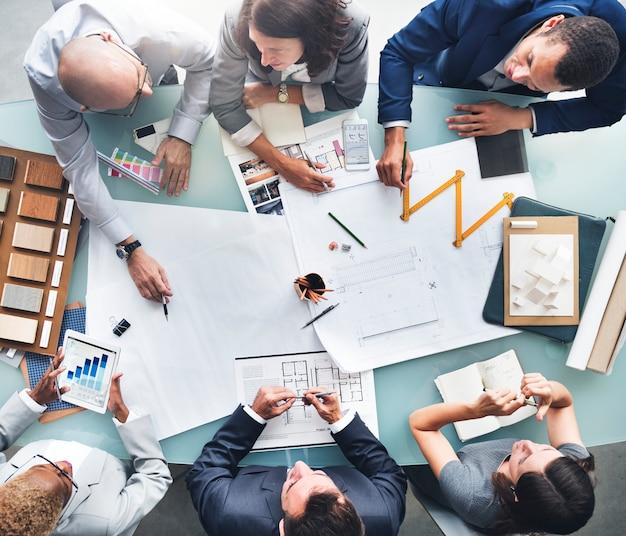 Bedrijfsmensen die het concept van de blauwdrukarchitectuur plannen