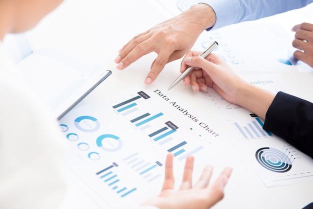 Bedrijfsmensen die het document van de gegevensanalysegrafiek bespreken