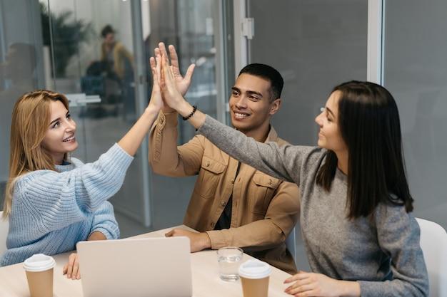 Bedrijfsmensen die high five geven, die in bureau samenkomen