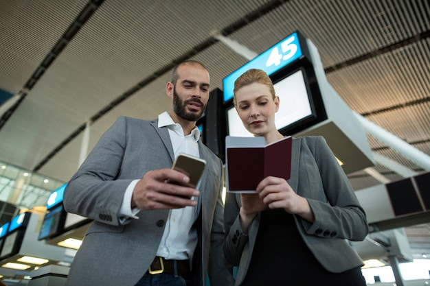 Bedrijfsmensen die instapkaart houden en mobiele telefoon gebruiken
