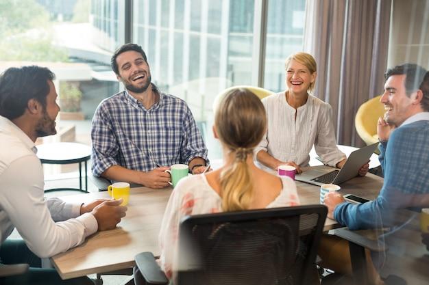 Bedrijfsmensen die koffiemok houden tijdens een vergadering