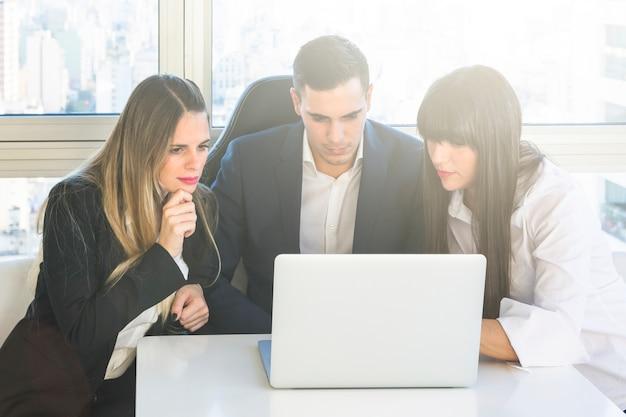 Bedrijfsmensen die laptop in de vergadering bekijken